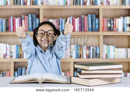 Smiling student showing ok gesture while sitting with book on desk in the library