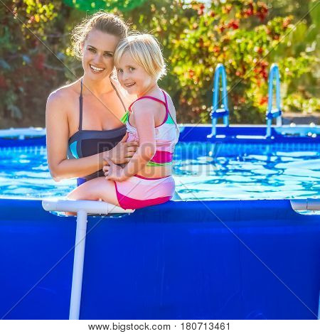 Smiling Healthy Mother And Child In Swimwear In Swimming Pool