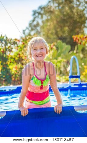 Smiling Active Child In Swimwear Playing In Swimming Pool