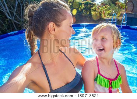 Smiling Healthy Mother And Child In Swimming Pool Taking Selfie