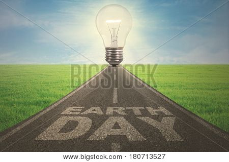 Earth Day concept. Empty street with a big light bulb and Earth Day text
