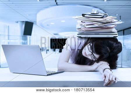 Image of a stressful female entrepreneur sleeping with a stack of burden on her head