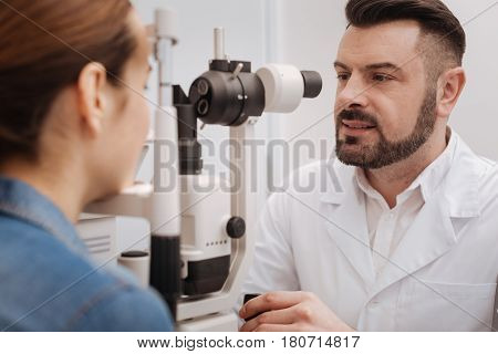 Professional examination. Pleasant good looking male oculist using the eye testing equipment and checking the eyesight of his patient while sitting at the table