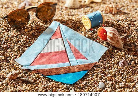 Patchwork block spool of thread pin cushion and sunglasses lie on sea stones of beach