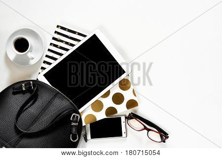 Women's office desk on white background touch pad tablet gadget cellphone with gold stylish books black handbag, top view. Mock up template, woman work place