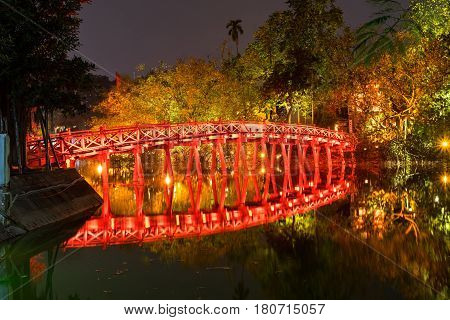 Night view of famous ancient wooden red-painted The Huc Bridge reflection on Hoan Kiem Lake at historic centre of Hanoi Vietnam.