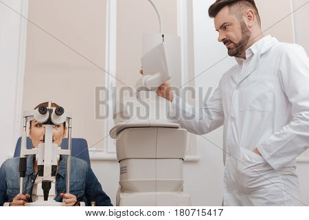 Sensory screen. Pleasant nice professional ophthalmologist looking at the screen and choosing certain regime while working with medical equipment