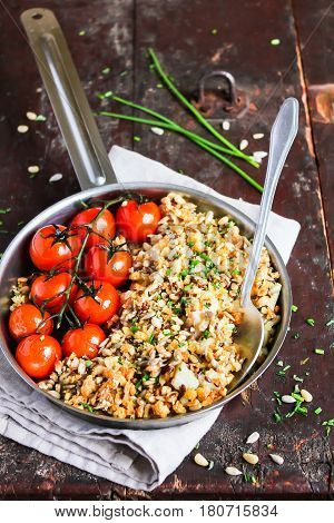 Baked cod fish fillet with crumbs, sunflower and flax seeds, roasted cherry tomatoes, chives in a pan on a wooden table, selective focus