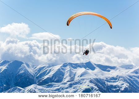 Parachute Sky-diver Flying In Clouds Above Mountains. Travel Adventure Concept. Space For Text