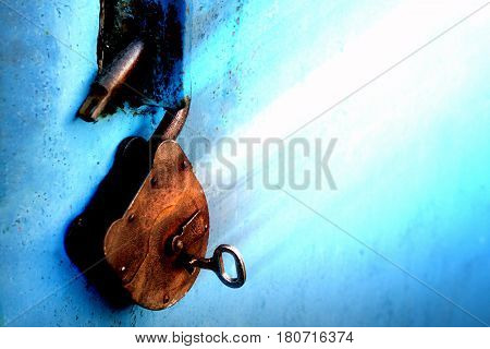 Old rusty lock with a key on a blue background.
