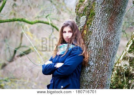 The girl is standing near the tree