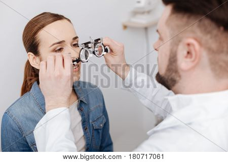 Vision examination. Professional nice male ophthalmologist holding eye test spectacles and putting them on his patient while preparing to do an eye test