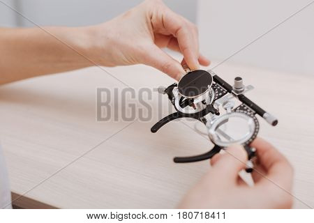 Be careful with them. Close up of eye test spectacles being held by a professional experienced nice ophthalmologist while being used for vision examination