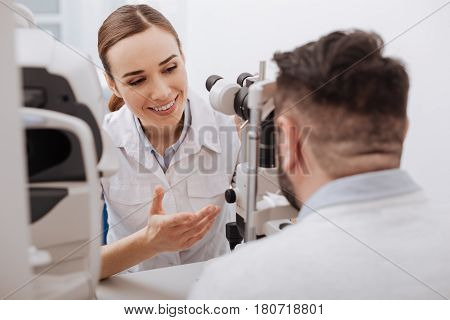 Friendly atmosphere. Delighted friendly female optometrist sitting opposite her patient and smiling while interacting with him
