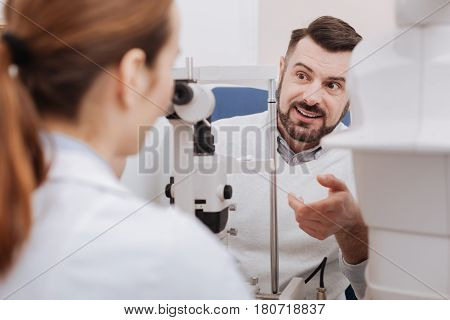 Concerning the eye test. Handsome bearded pleasant man looking at his doctor and asking her a question while being concerned about his eye examination results