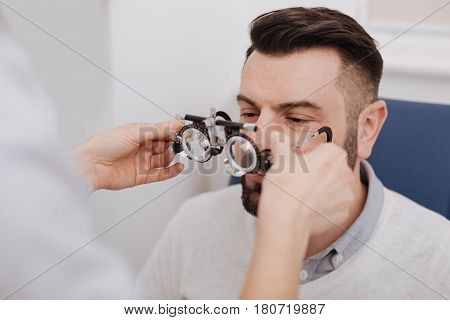 You need to wear them. Nice professional female doctor holding eye test glasses and giving them to her patient while testing his eyesight