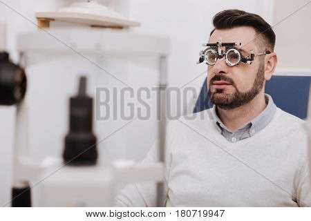 Ophthalmic problems. Nice bearded young man sitting in the chair and wearing eye examination glasses while having ophthalmic problems