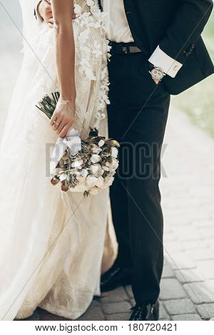 Luxury Wedding Couple Hugging And Holding Golden Bouquet Of Roses With Ribbons  In Park. Stylish Gro