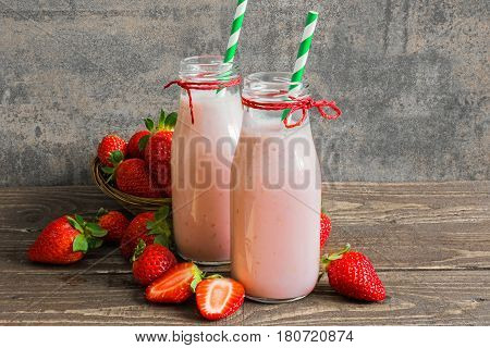 fresh strawberry smoothie in bottles with straw and fresh berries on rustic wooden table. healthy food and drink