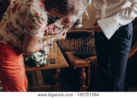 Mother Helping Groom Putting On Cuff Links, Getting Ready In The Morning In Hotel Room. Preparation