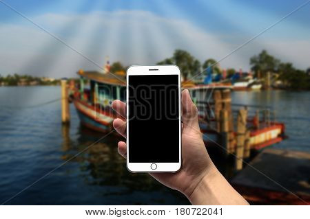 Blurred boat crossing the river in background with blank screen cell phone in hand in the foreground.