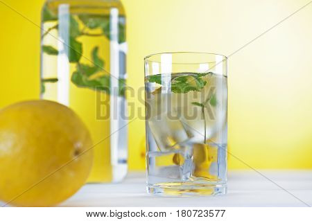 Cold water with lemon and mint on yellow background