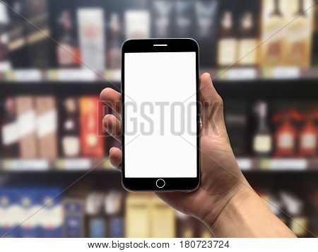 Blurred background of various liquor brands on the shelves, with blank screen cell phone in foreground. Copy Space.