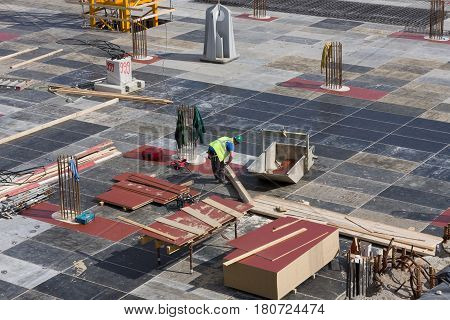 Concrete workers carpenters preparing construction formwork for concreting large building