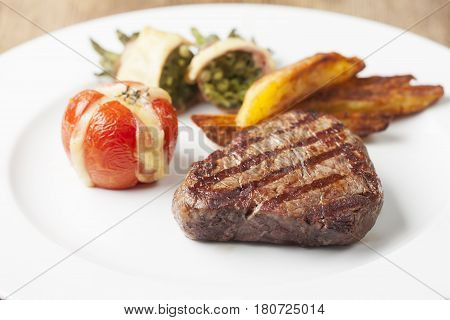 grilled steak with vegetables on a white plate