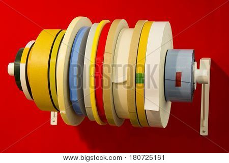 Variety double adhesive tape in; rolls of different types of tape with red background