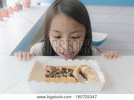 Asian kid impress Banana toast on the white table.