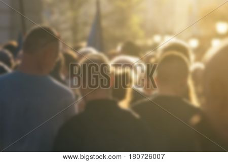 Defocused crowd attending political meeting large group of of unrecognizable people as audience to politician's speech outdoors