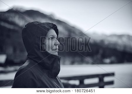 Beautiful female with hooded jacket outdoors looking up to the sky monochromatic image