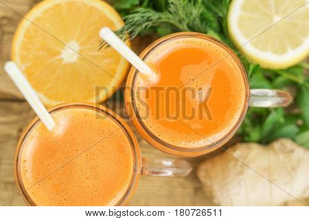Top View Of Carrot Smoothies In Glass Mugs With Orange And Lemon.