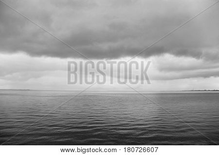 the landscape - the water and sky with clouds, monotone