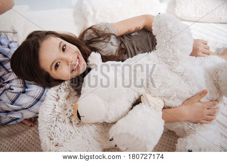 My fuzzy plush friend. Happy amused little girl lying on the bed at home while hugging fluffy bear and smiling