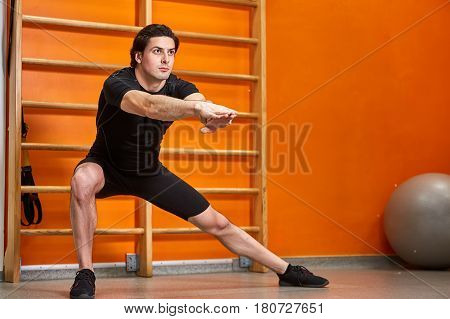 Sportsman in the black sportwear at the gym doing stretching exercises against bright orange wall. Stretching arms and legs. Man in the t-shirt, shorts and sneaclers. Portrait of the beautiful athletic man. Horizontal photo. Healthy lifestyle.
