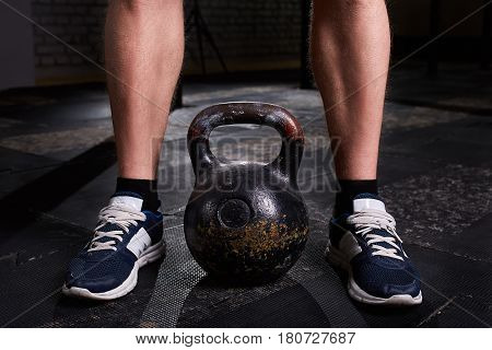 Closeup photo of young man's legs in sneackers and kettlebell against dark background. Crossfit workout. Detail of crossfit man. Healthy lifestyle.