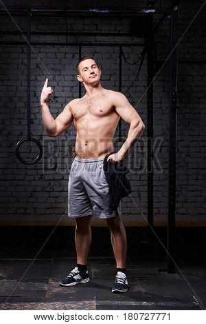 Portrait of strong young man working out crossfit against brick wall. Sportsman in the sportwear, shorts and sneackers. Concept of the crossfit activity. Healthy lifestyle.