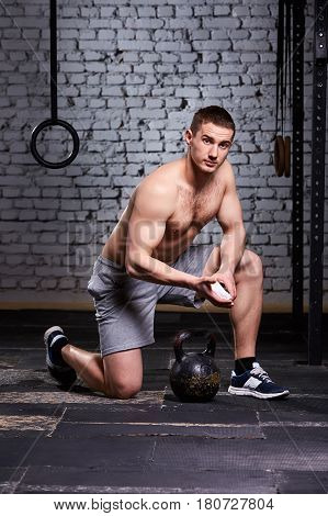 Young athlete man getting ready for crossfit training against brick wall. Sportsman in the sporty shorts and sneackers. On the floor is kettlebell. Horizontal photo. Healthy lifestyle.