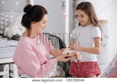 Taking care of my mother . Positive skilled cute kid sitting in the night nursery and caring about mother while using elastic roller and bandaging