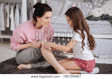 Priceless moments of motherhood. Cute skilled caring kid sitting in the night nursery and taking care of her mother while using adhesive bandage