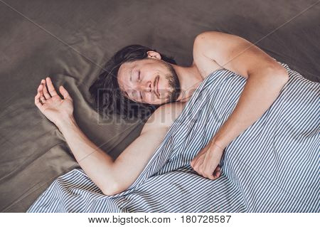 Beautiful Young Man Lying Down In Bed And Sleeping, Top View. Do Not Get Enough Sleep Concept