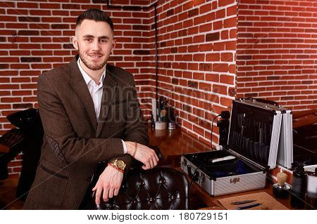Confident barber smiling expert looking at camera and keeping hand on chair while standing at barbershop. Interior of the barbershop, mirror and barber tools. Against brick wall. Master and professional.