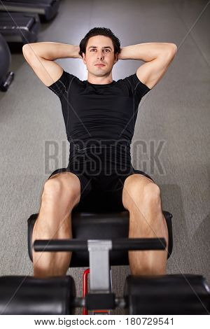 Athletic man in the black sportwear working with his abdominal on simulator in gym. Sportsman in the t-shirt and shorts. Energy and power. Healthy lifestyle.