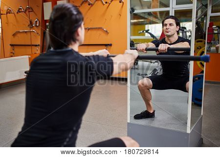 Young athletic man in black sportwear with bar of barbell flexing muscles in gym in front of the mirror. Sportsman in the t-shirt, shorts and sneackers. Power and energy. Exercises and squatting. Concept of the healthy lifestyle.