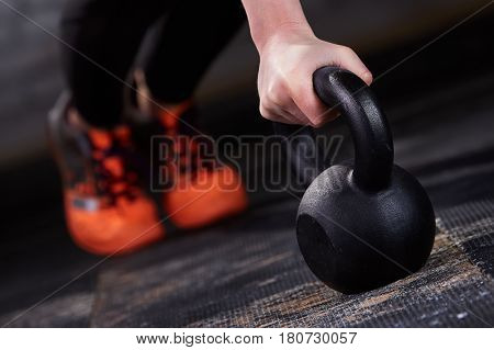 Closeup photo of young woman in the black leggings and orange sneackers while push-ups with kettlebell. Crossfit workout. Detail of crossfit woman. Healthy lifestyle.