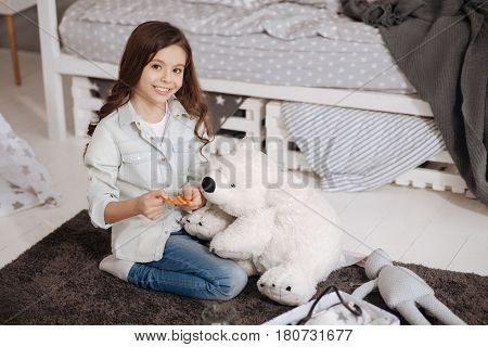 Pills for my friend. Smiling capable happy child sitting in the night nursery and enjoying being doctor while treating fluffy bear and holding pills