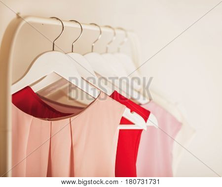 Women's clothing in pink tones on a white hanger. Selective focus.