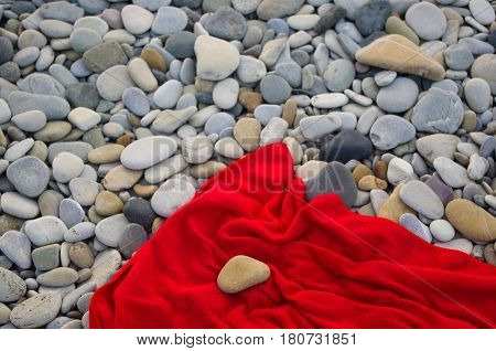 red towel and stone on pebble beach, sunset